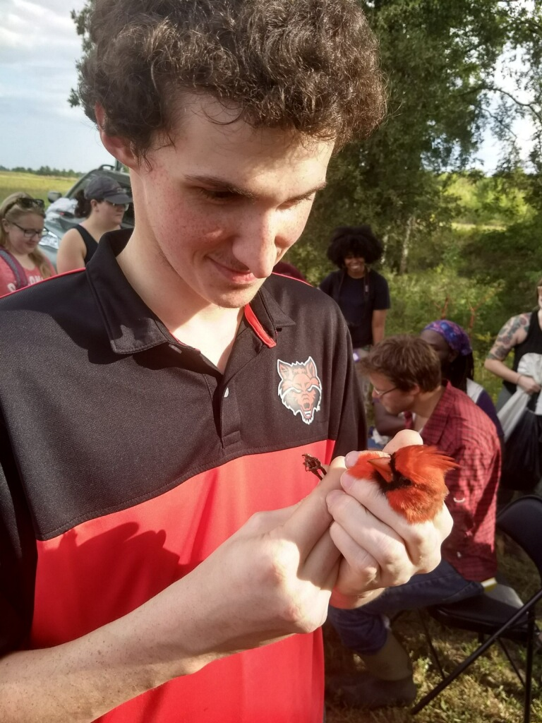 Biology student Gregory Daniels holding a cardinal