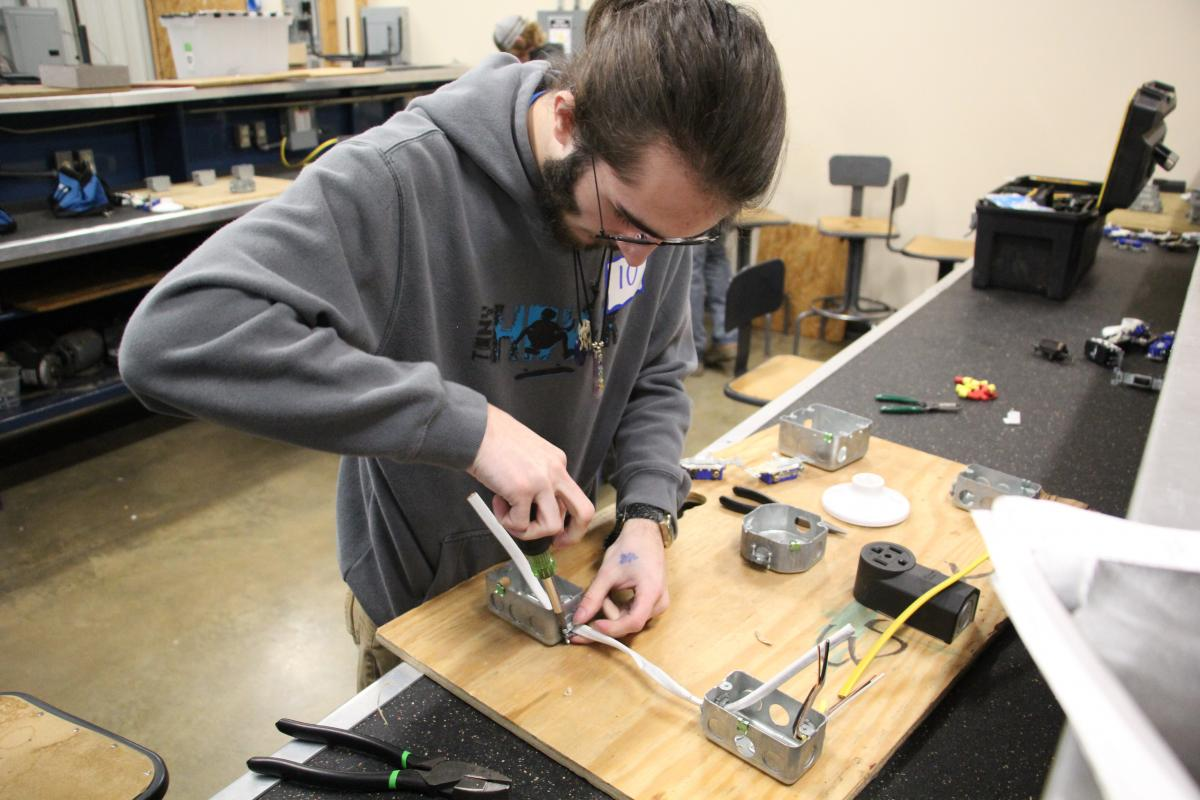 Student working on electrical circuit.