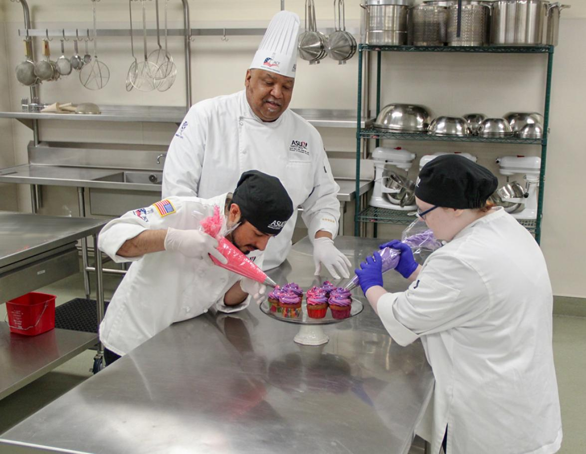 Hospitality Students icing cupcakes with instructor watching
