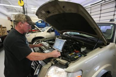 Student working on car with hood up and laptop sitting on engine