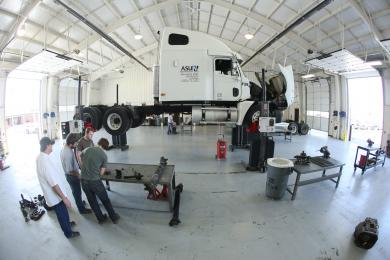 Diesel Truck in the air while students working on diesel engine parts in the foreground and background